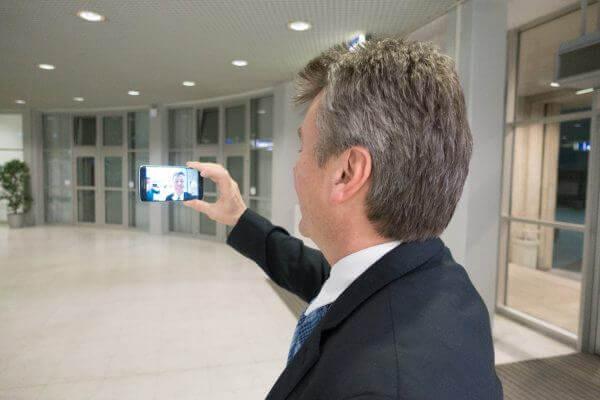 Christian macht einen Selfie-Aufsager mit dem Smartphone.
