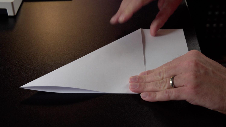 Zwei Hände falten einen Papierflieger